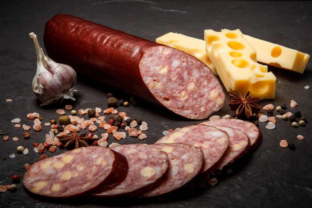 Delicatessen,sliced,cheddar,summer,sausage,with,sliced,pieces,served,with