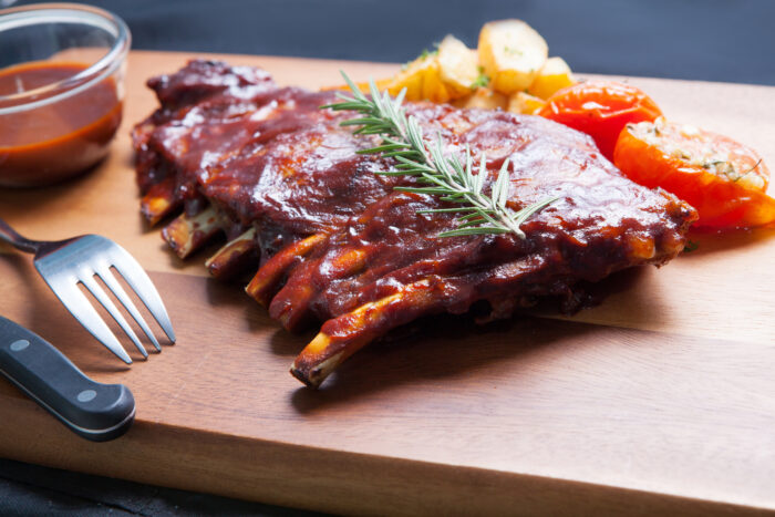 Pork,spareribs,with,tomato,and,fried,potatoes,on,wooden,plate
