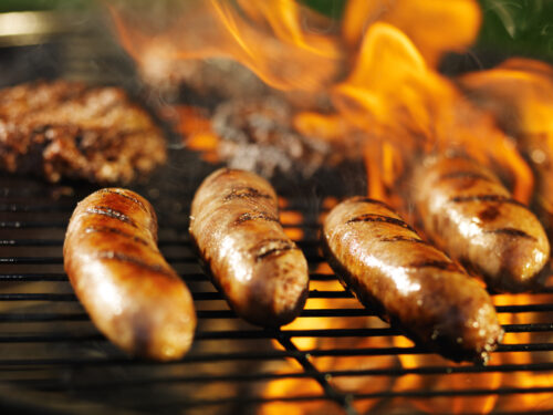 Bratwursts,cooking,on,flaming,grill